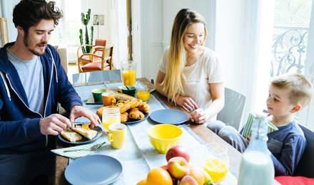 Tříčlenná rodina a její snídaně u stolu