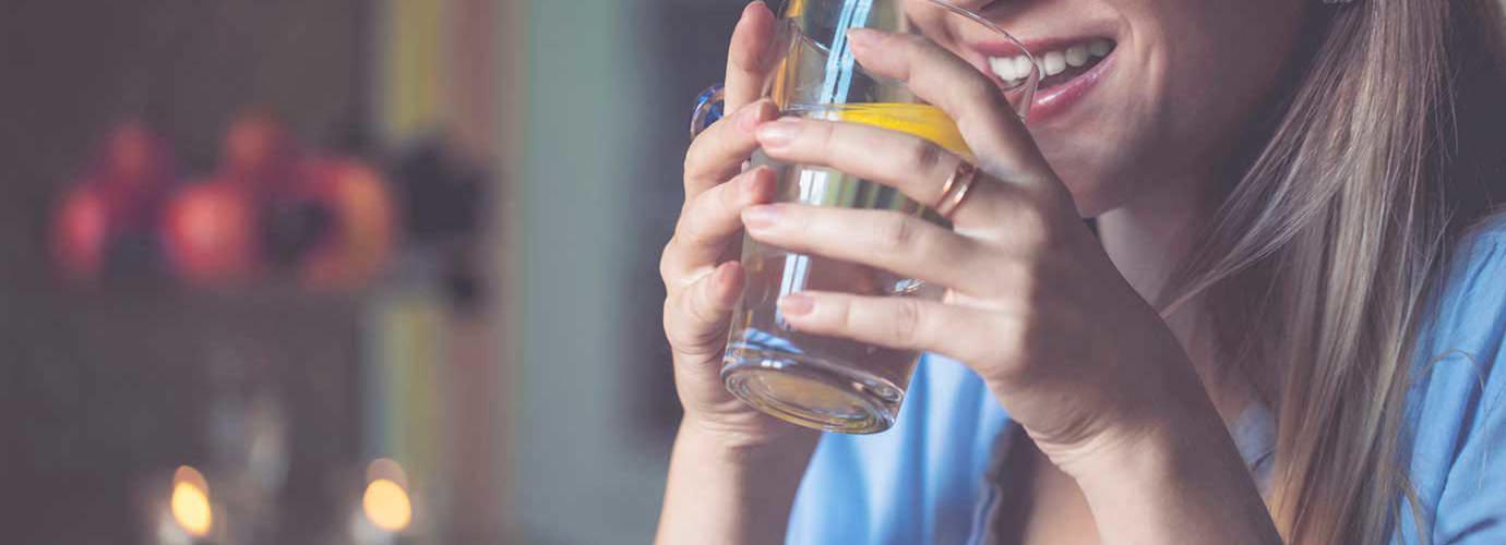 Žena se sklenicí vody s plátkem citronu