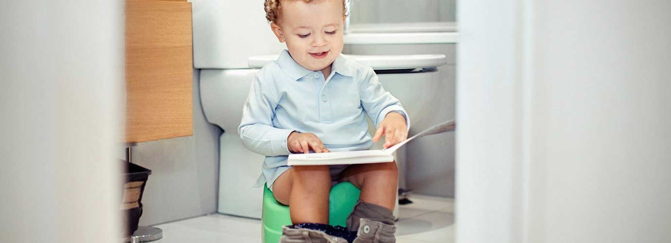 Chlapec na nočníku s knihou na klíně
