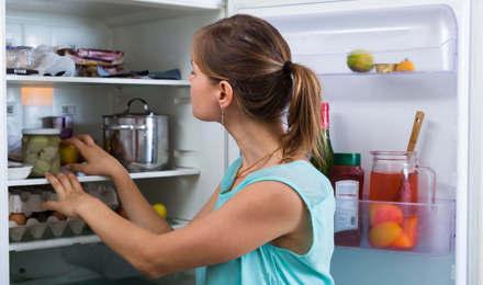 Женщина проверяет и чистит внутренние поверхности холодильника