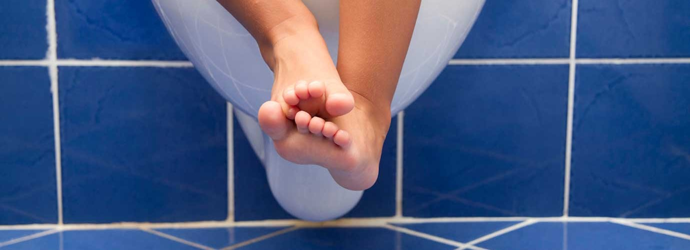 Dětské nohy visící z bílé závěsné toalety