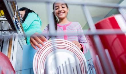 Девочка помогает ее матери на кухне загружая или разгружая посудомоечную машину