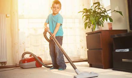 Мальчик чистит ковев пылесосом