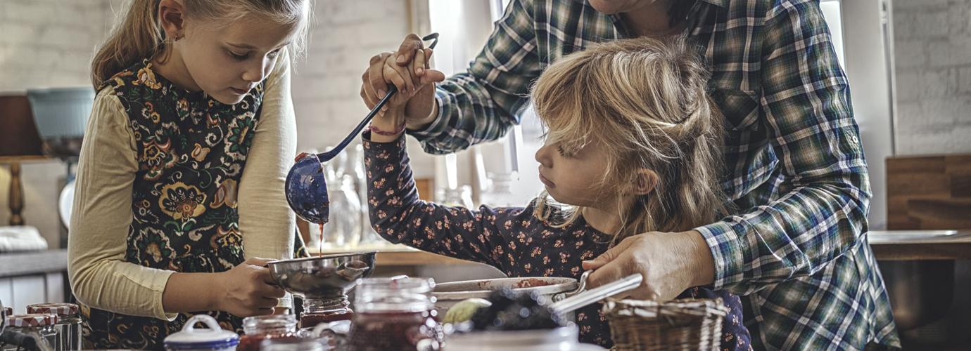 Мальчик пытается достать печенье в стеклянной банке руками