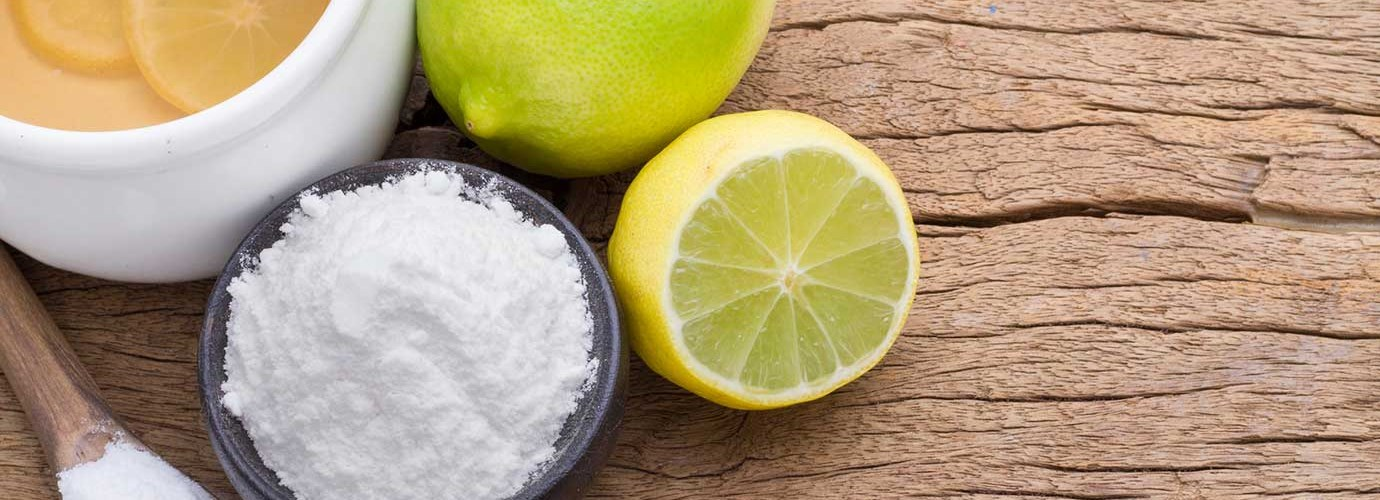 Натуральные моющие средства, такие как сода, в картонной коробке и апельсины рядом с желтым аэрозолем и небольшой стеклянной бутылкой