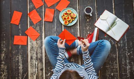 Egy nő Valentin-napi kártyákat ír házi készítésű Valentin-napi ajándékokkal, a földön ülve