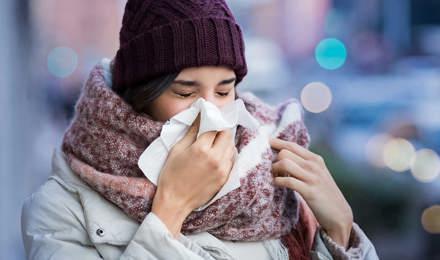 Nő bebugyolálva vastag téli ruházatba arcüreggyulladás tüneteivel, egy zsebkendőbe tüsszögve