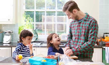 Отец готовит обед рядом с двумя детьми на кухне