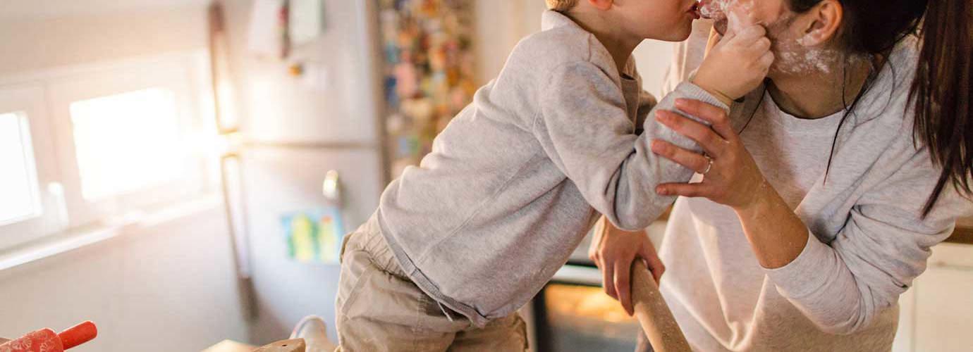 Молодой мальчик и его мать играют с тестом и мукой на кухне