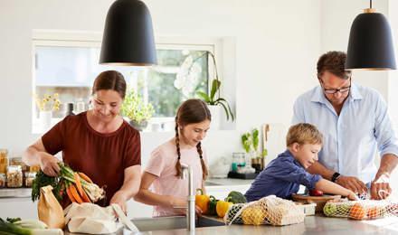 Мама и папа учаи ребенка перерабатывать, распаковывая еду из переработанной упаковки на кухне