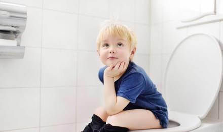 Ein Kleinkind sitzt auf einer Toilette