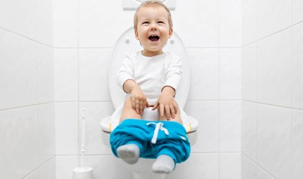 Ein kleines Kind sitzt mit heruntergelassener blauer Hose auf einer Toilette