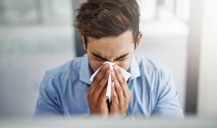 Fiatalember tüsszög és fújja az orrát egy zsebkendőbe