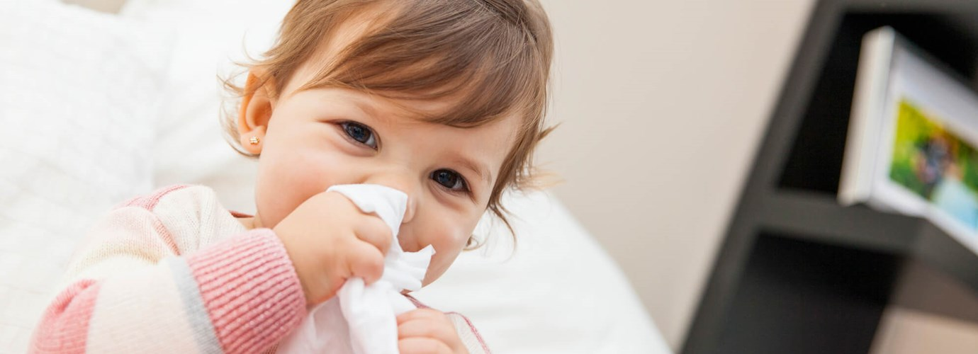 Маленька дівчинка витирає ніс серветкою