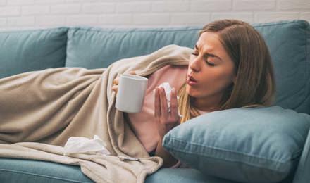 Жінка, лежачи на дивані, кашляє, тримаючи чашку чаю і серветки