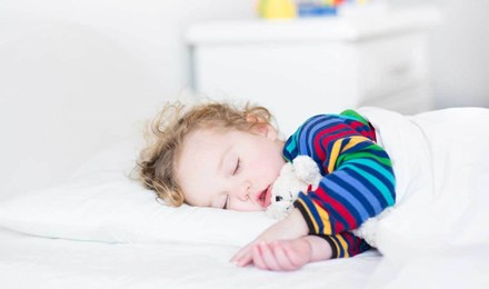 Ein kleines Mädchen liegt schlafend in einem Bett