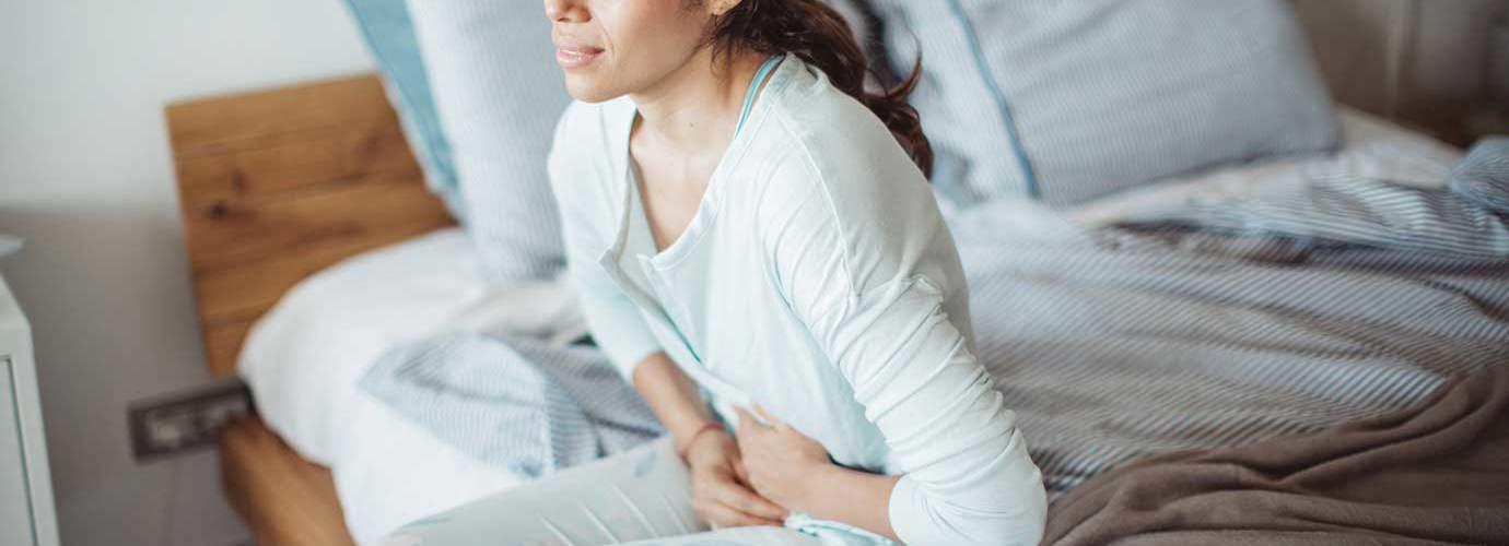 Eine Frau sitzt mit Schmerzen im Unterleib auf einem Bett
