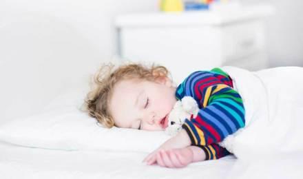 Maleni dječak spava u krevetu