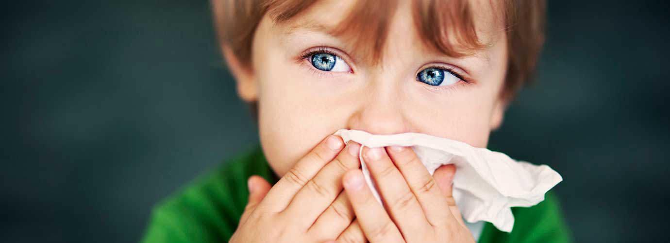 Ένα αγόρι με αλλεργία στη σκόνη κρατά ένα χαρτομάντιλο μπροστά από τη μύτη του