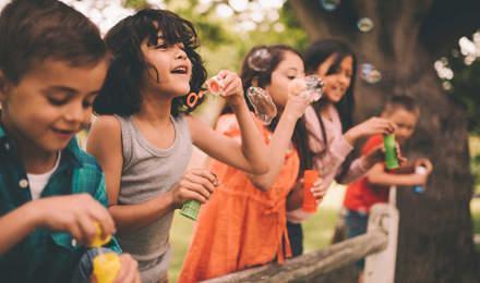 Μια ομάδα παιδιών στέκεται σε έναν ξύλινο φράχτη και κάνει σαπουνόφουσκες το καλοκαίρι