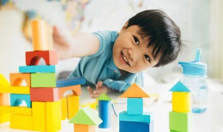 Ένα αγόρι παίζει με πολύχρωμα ξύλινα παιχνίδια