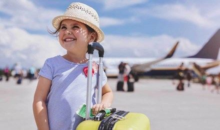 Ένα κορίτσι με αεροπλάνο στο φόντο χαμογελά ενώ κρατά μια κίτρινη βαλίτσα με τα απαραίτητα των οικογενειακών διακοπών