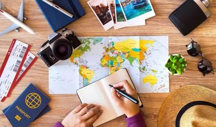 Ένα τραπέζι με διαβατήρια, χάρτες, γυαλιά ηλίου, σημειωματάριο και αεροπορικά εισιτήρια