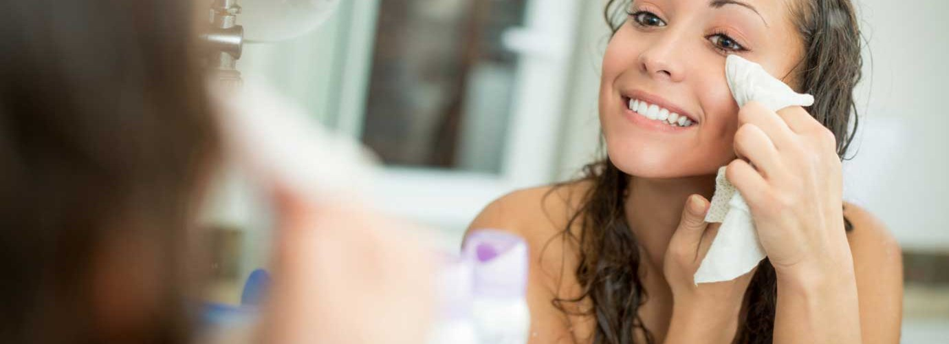 Nő mosolyog, miközben eltávolítja a sminket egy törlőkendővel