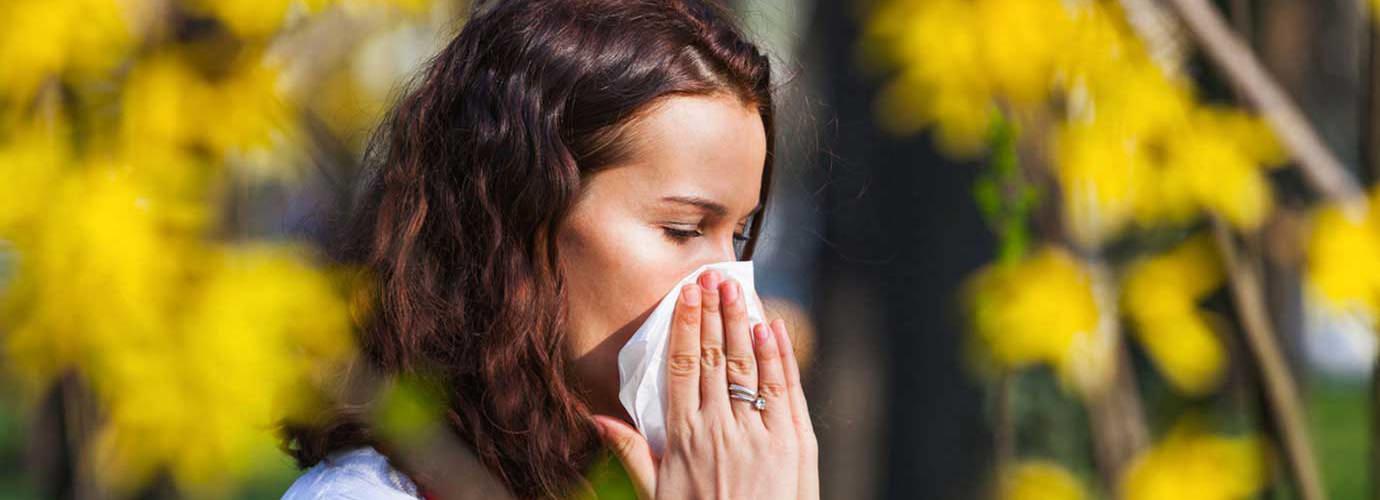 Молода жінка чхає у серветку посеред польових квітів