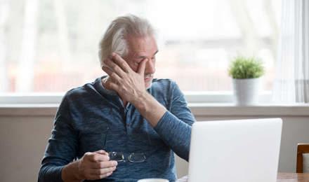 У літнього чоловіка, який сидить за комп'ютером, свербить одне око