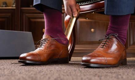 Férfi barna polírozott bőrcipőt visel