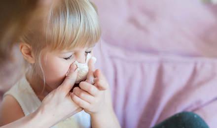 Egy anya segít lányának fújni az orrát papír zsebkendővel