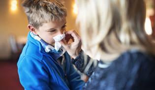 Egy anya fújja a gyermeke orrát, aki azon tűnődik, mit kell tenni, hogy megakadályozza a betegség terjedését