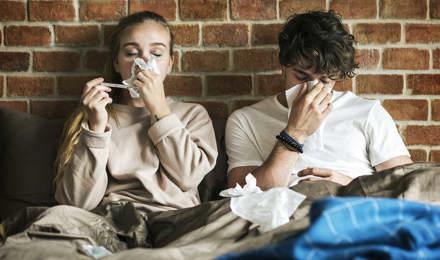 Két fiatal ül a takaró alatt tüsszögve egy zsebkendőbe, egy téglafallal a háttérben