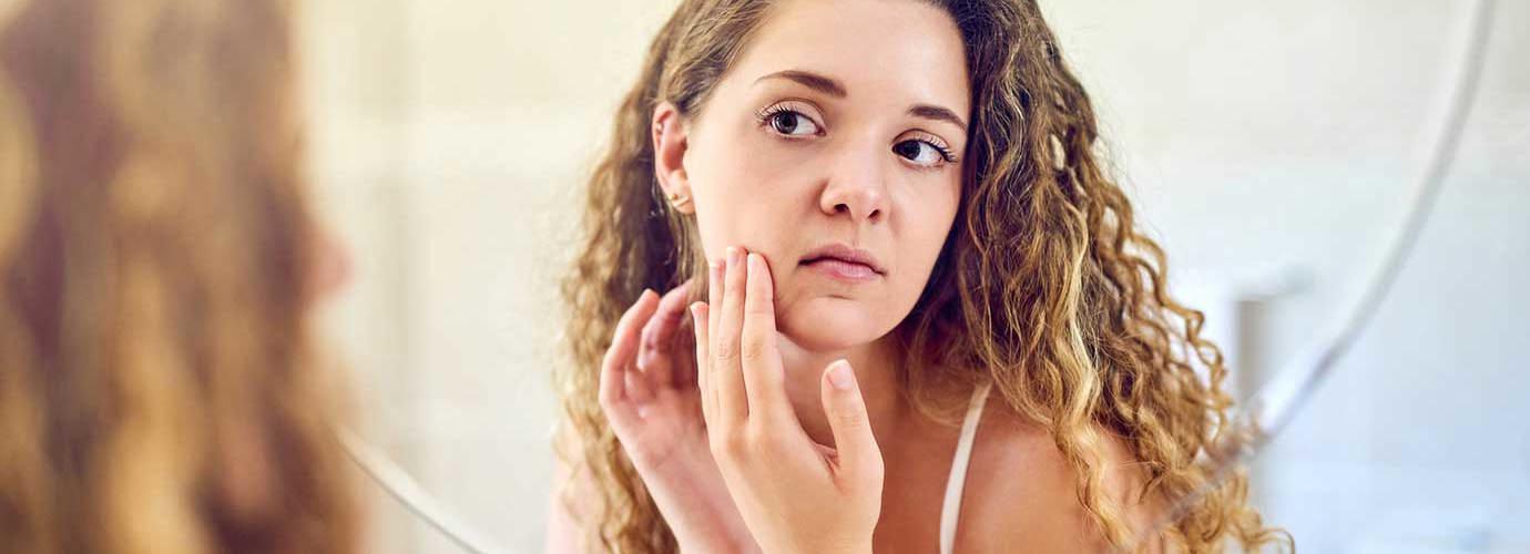 Една млада жена изстискване пъпка на мазна кожа и я погледнете в огледалото