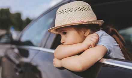 Copil cu greață în mașină purtând o pălărie în timp ce