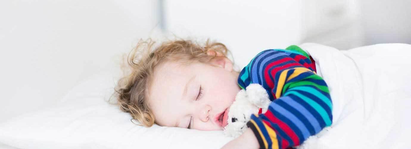 Fetiță doarme pe un pat