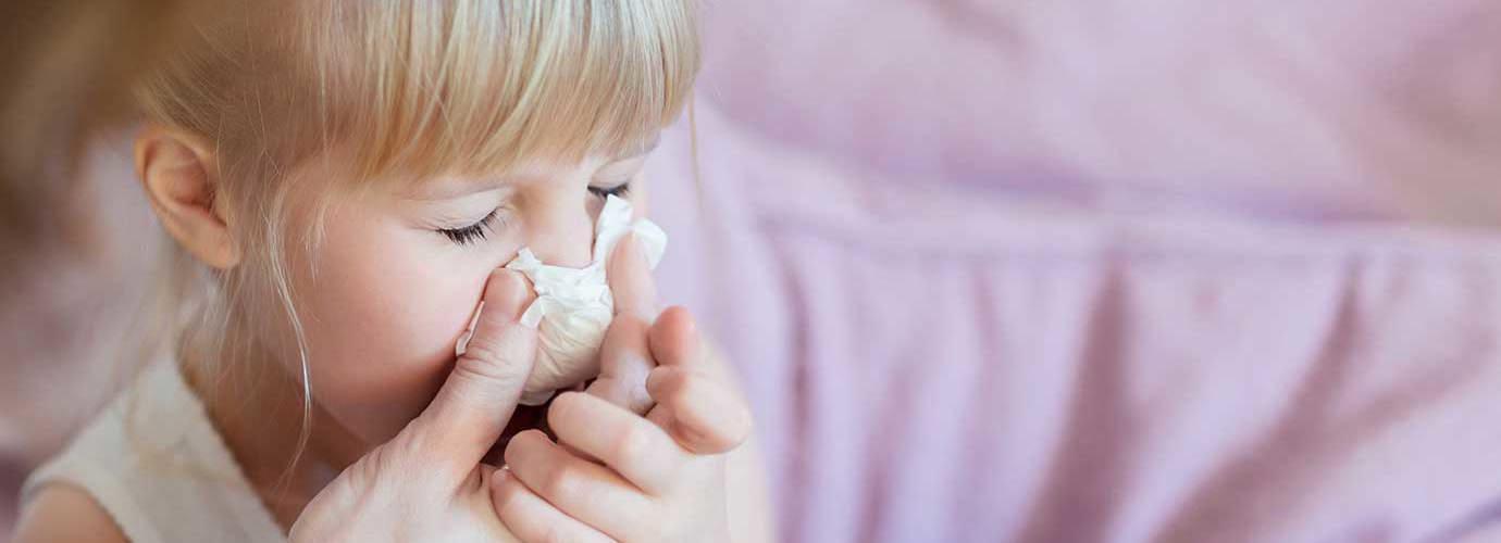 O mamă își ajută fiica să sufle nasul cu șervețel de hârtie