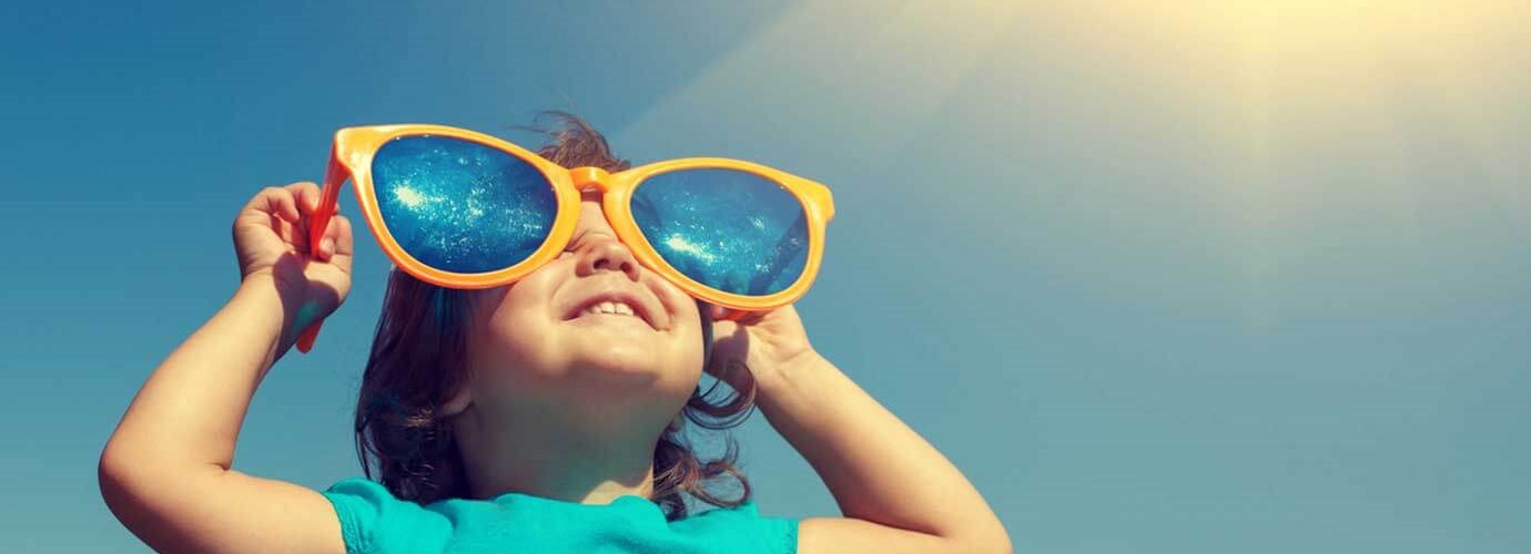 O tânără copilă, purtând în mod hilar o pereche prea mare de ochelari de soare, într-o zi senină, luându-și doza de vitamina D de la soare