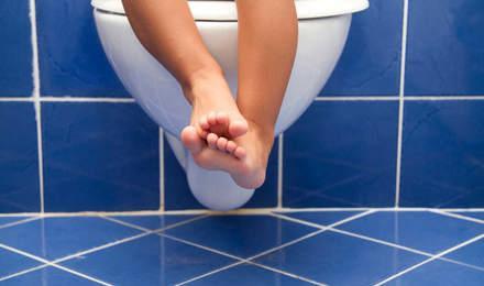 Ноги малюка звисають з сидіння туалету білого кольору