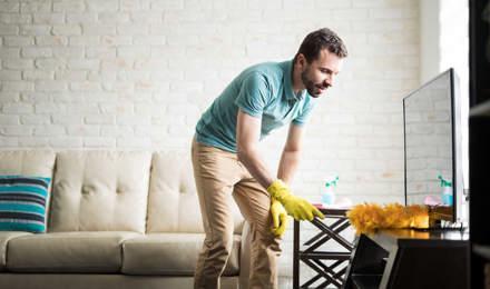 Человек потирает от пыли свой дом с тряпкой