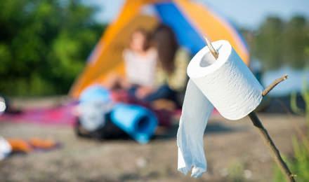 Eine Rolle Toilettenpapier auf einem Stock aufgespießt mit einem Campingplatz im Hintergrund