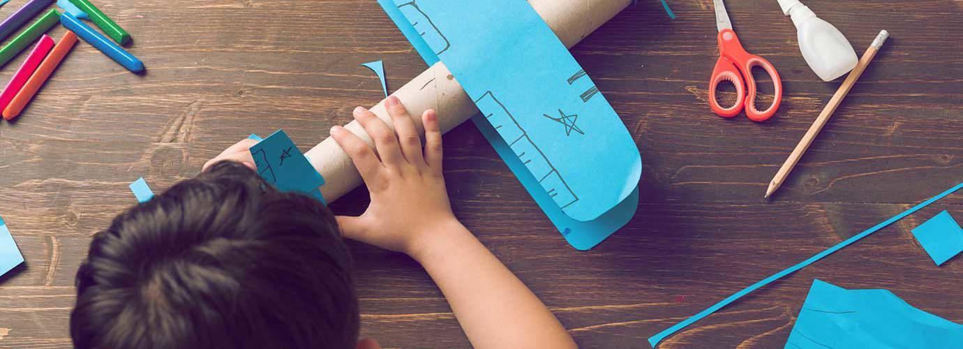 Ein Kind bastelt ein Flugzeug aus Pappe
