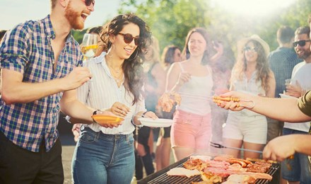 Eine Gruppe von Freunden bei einer Grillparty stehen um einen Grill herum