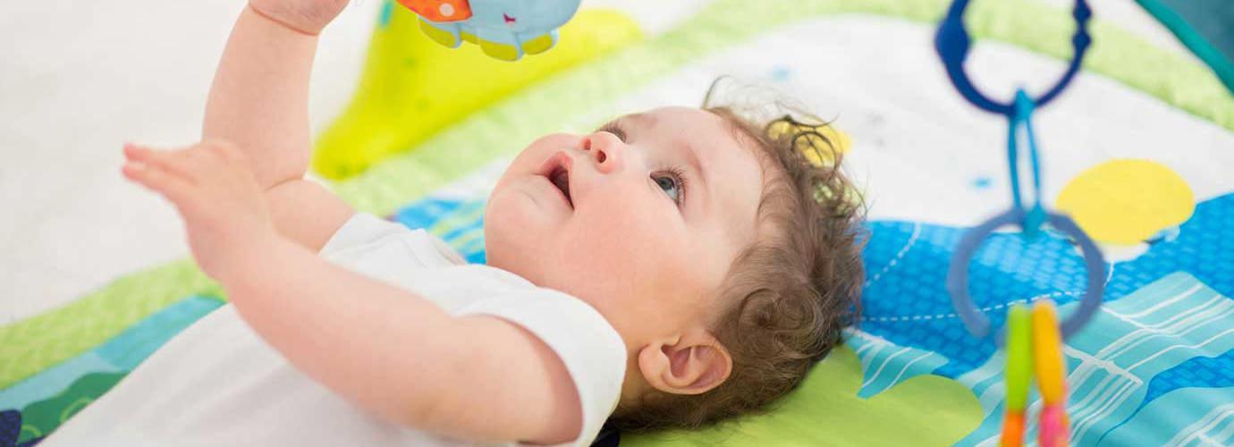 Ein Baby liegt auf einer bunten Spielmatte und schaut zu einem Mobile auf