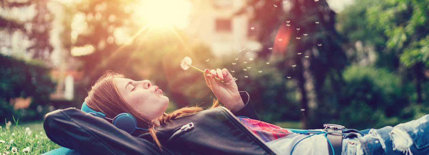 Eine junge Frau liegt auf dem Rasen, hört Musik und pustet eine Pusteblume