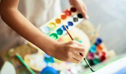 Ein Kind malt mit einem Pinsel auf einer Leinwand und hält eine Farbpalette in den Händen