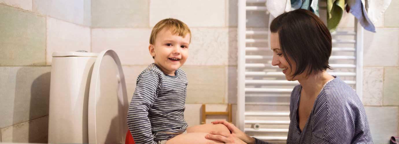 Eine Mutter hilft ihrem Sohn, der im Badezimmer auf einem Töpfchen sitzt