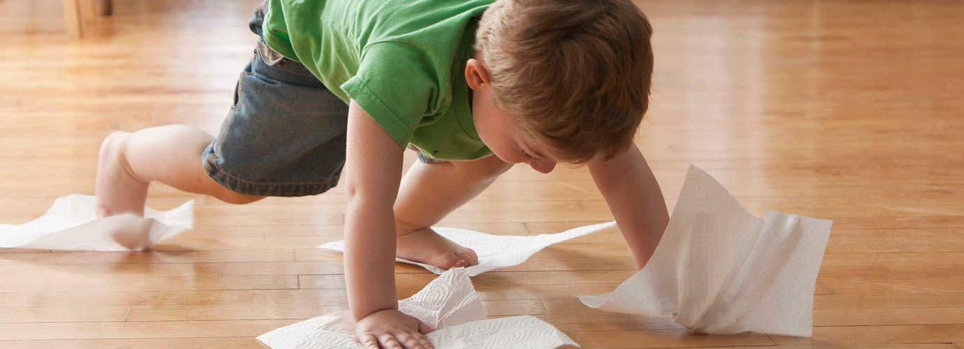 Copil care curăță podeaua cu prosoape de hârtie