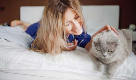 Женщина лежит на кровати, поглаживая кошку, и не представляет симптомы аллергии на кошек